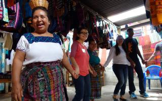 """Students and faculty member Christina Lee traveled to Guatemala for the course """"Identity in the Hispanic World"""" and captured photos and thoughts about the experience, which follow. In this photo: After women at a weaving co-op demonstrated how they create their textile art, they showed us a traditional Kaqchikel dance from Santiago de Zamora and invited us to dance with them. A couple of the women had baskets, which contained flower petals. They scattered these petals on the floor and on some of our class"""